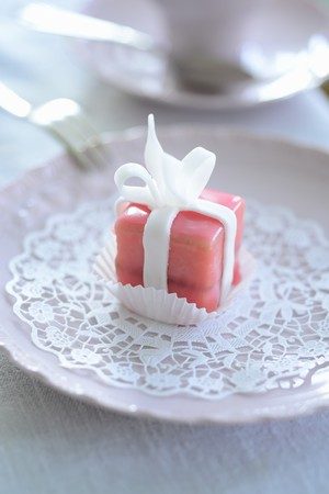 pinky: A pink petit four on a paper doily