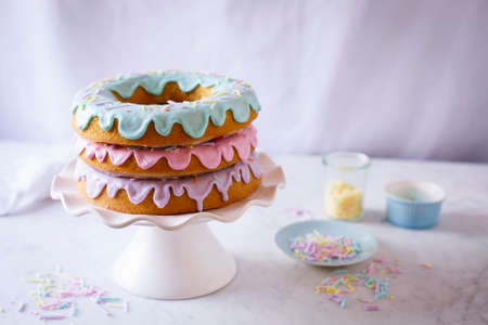 A doughnut cake with three pastel coloured glazes