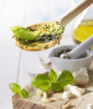 A wooden spoon with pesto and a basil leaf LANG_EVOIMAGES
