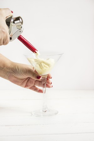 A whipped cream dispenser and cream in a glass