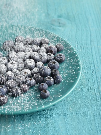 Blueberries on blue plate on blue table