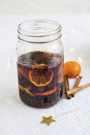 clementines: Homemade rum punch with clementines, raisins, cinnamon and lemon zest in a glass jar