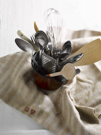 vintage: A small jug with old kitchen utensils