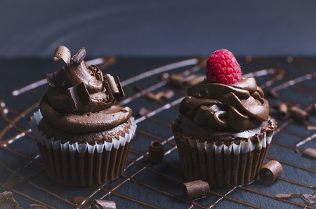 Decadent chocolate cupcakes with chocolate icing, shavings of chocolate and a raspberry
