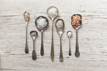whiteness: Seven vintage spoons of diffrent types of salt on a white wooden surface