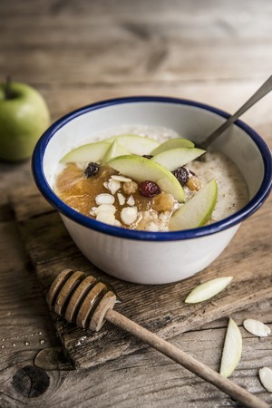 pip: A bowl of porridge with apple puree, sultanas, almond, honey and apple slices