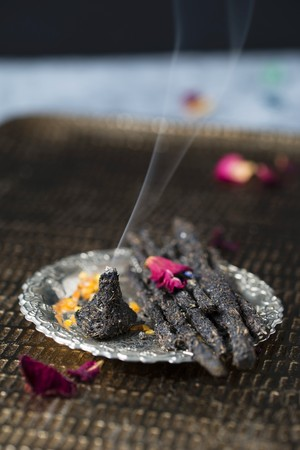 Homemade incense sticks and a cone made of charcoal, resin and dried herbs and flowers