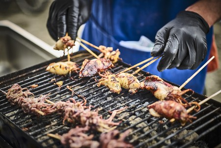 broiling: Calamari pieces on a grill in a street kitchen