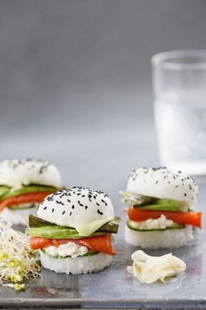 crossover: Three sushi burgers with smoked salmon, cucumber, fresh cheese, wasabi, nori and avocado