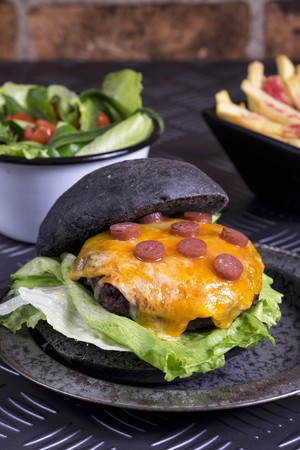 Beef burger with melted cheese in a black bun LANG_EVOIMAGES
