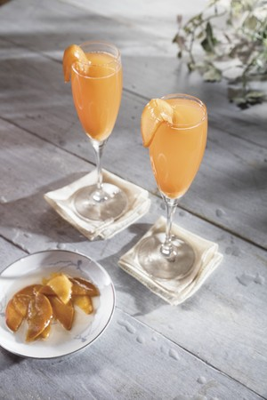 Whiskey cocktail in champagne flute with macerated peaches garnish