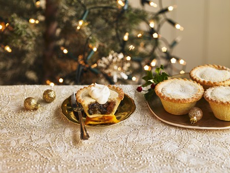 A plate of filled mince pies and one mince pie cut open with a dollop of cream LANG_EVOIMAGES