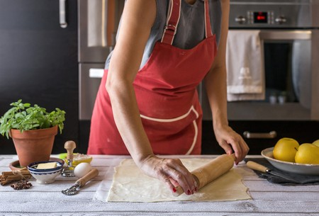 worktops: Woman rolls out dough for apple pie LANG_EVOIMAGES