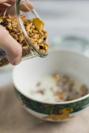 Granola being poured into a bowl of milk