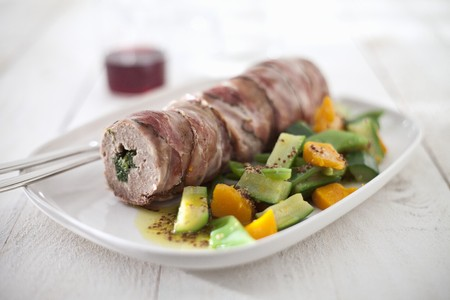 Mince roll with a spinach filling wrapped in bacon and cooked in a broth