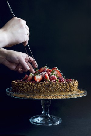 gateau: A chocolate cake topped with strawberries, pomegranate seeds and nuts