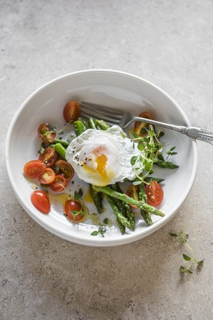 A poached egg on a bed of asparagus with cherry tomatoes LANG_EVOIMAGES