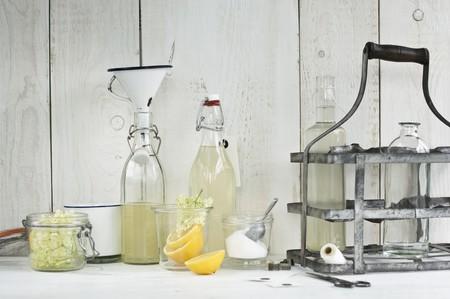 halved  half: Homemade elderflower cordial in bottles, fresh elderflowers, lemon halves, sugar, a funnel and small bottle labels