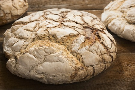 woodfired: Large loaves of bread baked in a wood-fired oven on a wooden surface