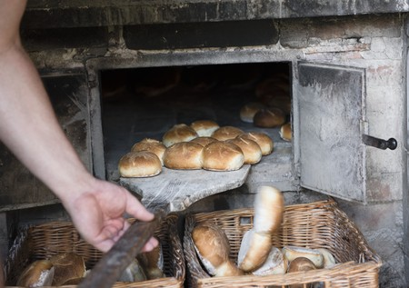 reportage: A man sliding bread rolls out of the oven and into wicker baskets