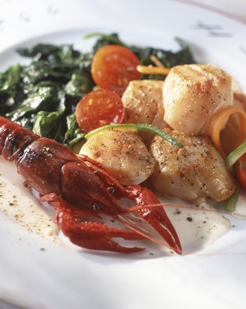 Pan-fried scallops and crayfish with spinach and tomatoes