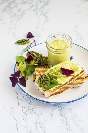 Broad bean hummus with toast and salad leaves