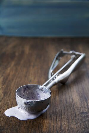 Ice cream scoop with melted ice cream in it