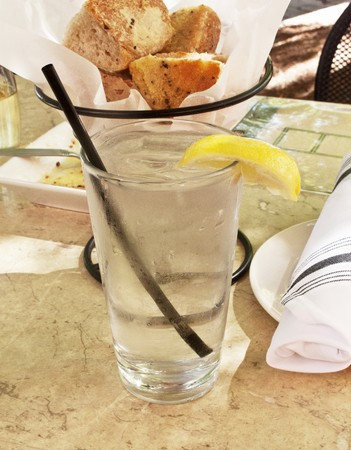 lemon wedge: A glass of ice water with a slice of lemon at a restaurant