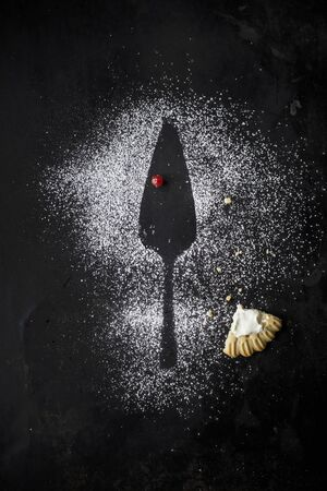 Leftover berry tart and the silhouette of a cake slice in icing sugar LANG_EVOIMAGES