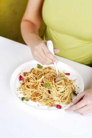 A woman eating spaghetti with anchovies LANG_EVOIMAGES