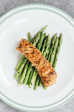 Grilled salmon fillet on a bed of green asparagus