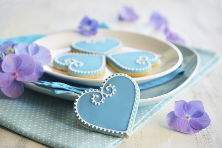 whiteness: Heart-shaped biscuits decorated with blue and white icing served on a plate with flowers