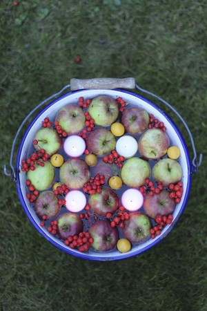ides: Floating candles, apples and berries in a bucket of water as an autumn decoration