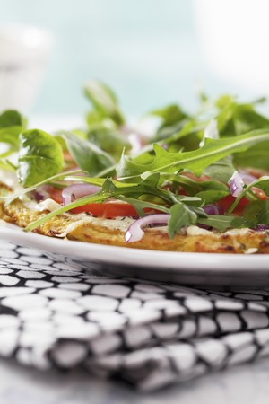 Gluten-free Romanesco broccoli pizza with rocket and tomatoes