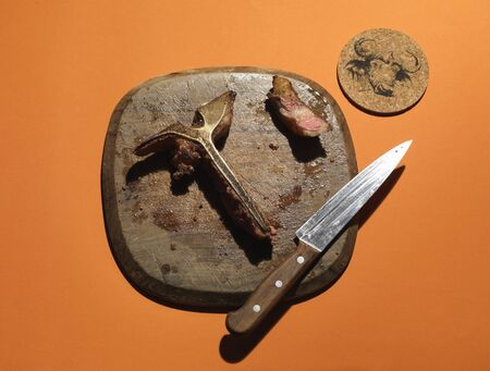 The leftovers of a T-bone steak on a wooden board LANG_EVOIMAGES