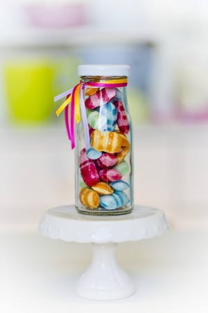 colored bottle: Colourful sweets in a small glass bottle