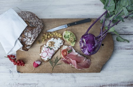 Slices of bread with various toppings on a chopping board with redcurrants, purple kohlrabi and crusty bread LANG_EVOIMAGES