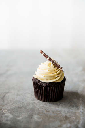 whiteness: A chocolate cupcake with white chocolate cream on a marble surface. LANG_EVOIMAGES