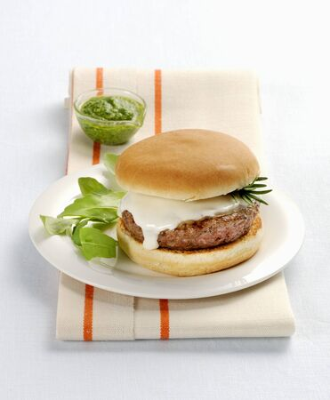 A hamburger with scamorza and basil pesto