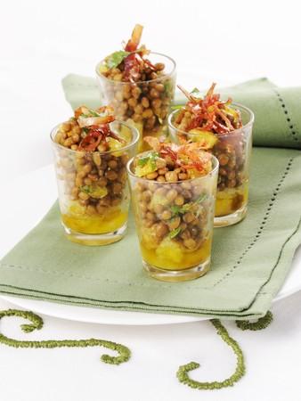 Lentil salad with oranges and strips of ham served in glasses