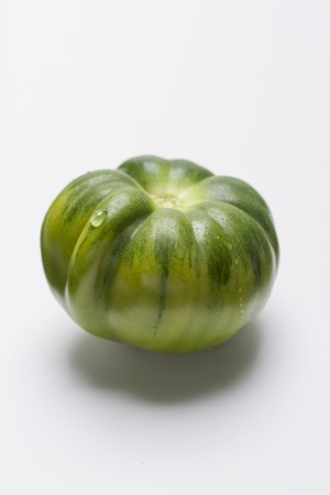 A green tomato on a white surface LANG_EVOIMAGES