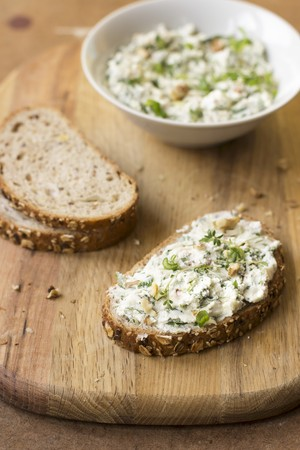 A slice of bread with goats cheese, spring onion, dandelion greens, thyme and walnuts LANG_EVOIMAGES