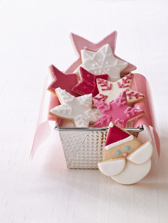 Star shaped Christmas biscuits in a loaf tin next to a Father Christmas biscuit