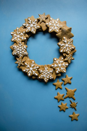 ides: A wreath made of iced gingerbread stars on a blue background LANG_EVOIMAGES