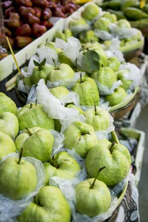 Fresh guavas wrapped in foil at a market in Thailand LANG_EVOIMAGES