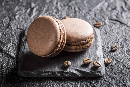 Macaroons with coffee beans on a black stone LANG_EVOIMAGES