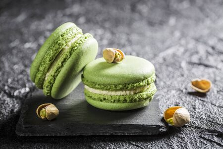 Pistachio macaroons on a black stone LANG_EVOIMAGES