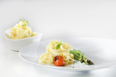 Tagliatelle with sautéed cherry tomatoes, basil and green asparagus with a bowl of mashed parsley potatoes in the background LANG_EVOIMAGES
