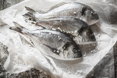 Three seabream on a piece of white paper with salt crystals LANG_EVOIMAGES
