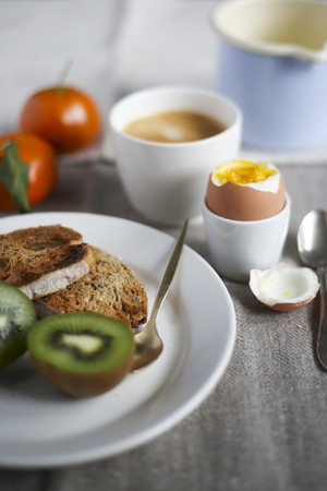 Breakfast with a soft boiled egg, fresh fruit, toast and coffee